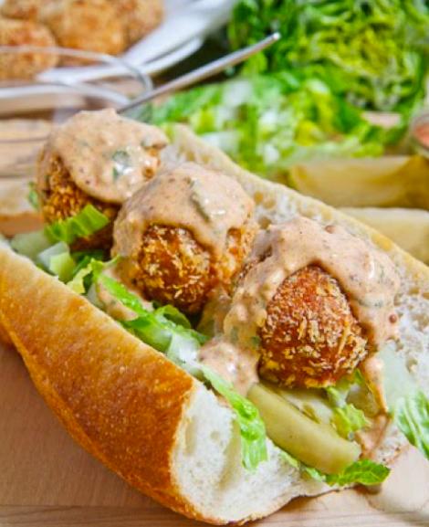 Sandwich de corquetas sobre ensalada y salsa