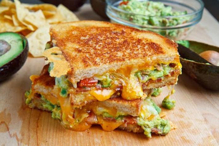 Sandwich de pan rústico con gucamola, bacon y queso chedar