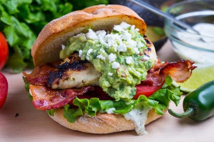 Sandwich en bollo redondo rústico de pollo, bacon, guacamole, tomate, lechuga y mayonesa de jalapeño