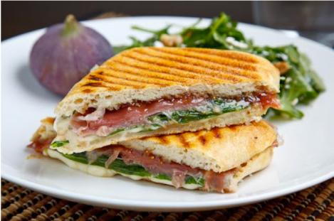 Sandwich planchado de jamón, queso, rúcula y mermelada de higos, a la parrilla.